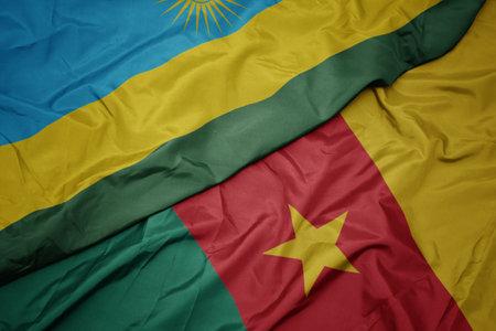 waving colorful flag of cameroon and national flag of rwanda. macro Stock Photo