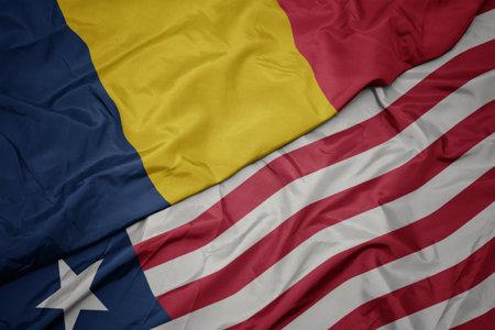 waving colorful flag of liberia and national flag of chad. macro