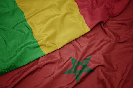 waving colorful flag of morocco and national flag of mali. macro