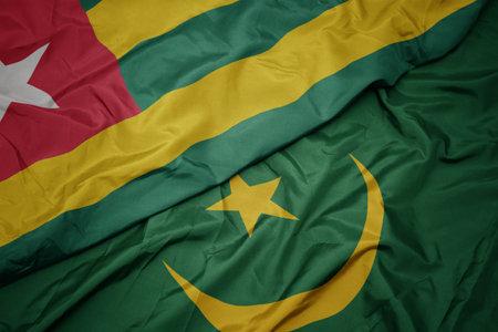 waving colorful flag of mauritania and national flag of togo. macro