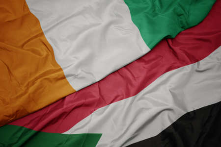 waving colorful flag of sudan and national flag of cote divoire. macro Stock Photo