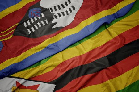 waving colorful flag of zimbabwe and national flag of swaziland. macro Stock Photo