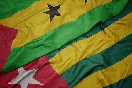 waving colorful flag of togo and national flag of sao tome and principe . macro