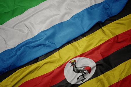 waving colorful flag of uganda and national flag of sierra leone. macro