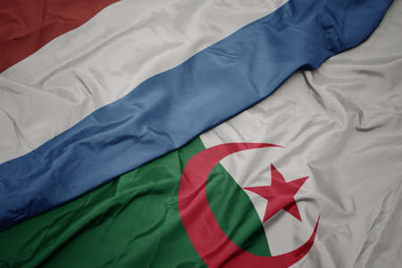 waving colorful flag of algeria and national flag of luxembourg. macro