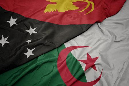 waving colorful flag of algeria and national flag of Papua New Guinea . macro