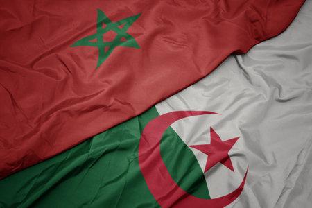 waving colorful flag of algeria and national flag of morocco. macro