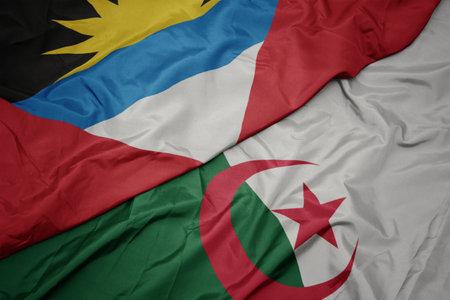 waving colorful flag of algeria and national flag of antigua and barbuda. macro