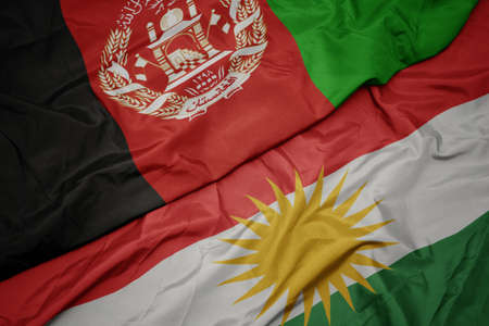 waving colorful flag of kurdistan and national flag of afghanistan. macro