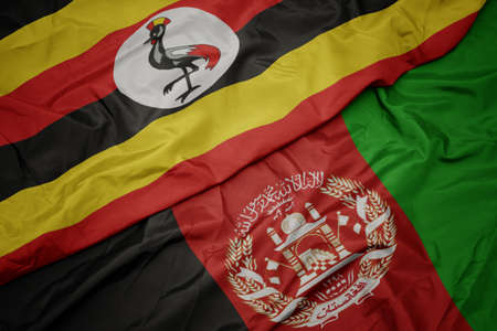 waving colorful flag of afghanistan and national flag of uganda.
