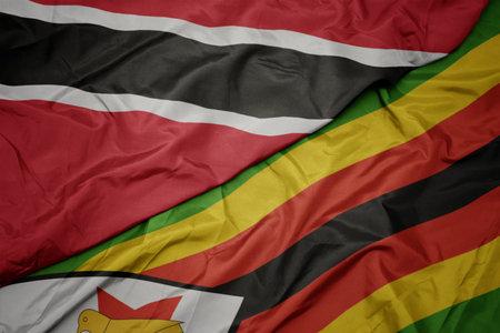 waving colorful flag of zimbabwe and national flag of trinidad and tobago. macro