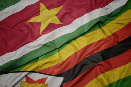 waving colorful flag of zimbabwe and national flag of suriname. macro Stock Photo