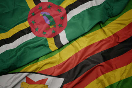 waving colorful flag of zimbabwe and national flag of dominica. macro Stock Photo