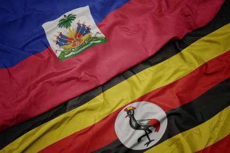 waving colorful flag of uganda and national flag of haiti. macro