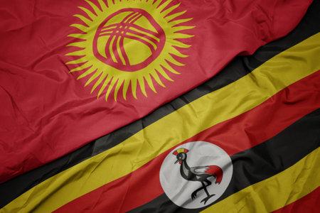 waving colorful flag of uganda and national flag of kyrgyzstan. macro