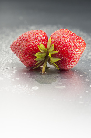 uncluttered: Two ripe strawberries in mouth shape  Vertical shoot in studio on silver background with copy space  Dew and droplets suggest freshly harvested  Still life