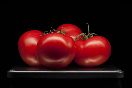 Four red ripe tomatoes on tray with luxury black background  Clean line photo