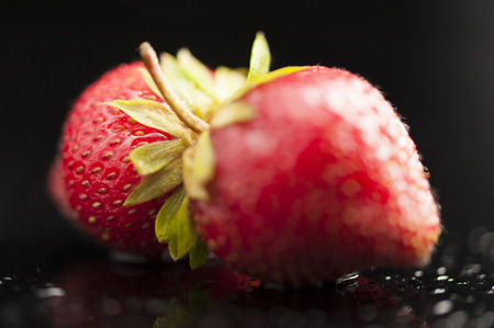 uncluttered: Twin ripe strawberries on wet and black background in studio  Focus  Dew and droplets suggest freshly harvested