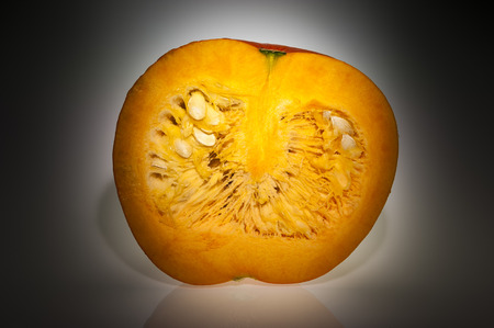 longitudinal: Single orange pumpkin with front longitudinal section after freshly harvest in autumn  We can see pulp and seeds  Shooting studio with very focus lighting  Stock Photo
