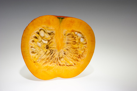 longitudinal: Single orange pumpkin with front longitudinal section after freshly harvest in autumn  We can see pulp and seeds  Shooting studio  Background in light gray gradation