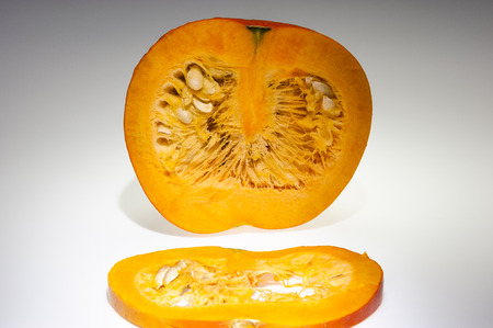 longitudinal: In the foreground on slice of orange pumpkin  We can see also pulp and seeds in the background on the cutting pumpkin with front longitudinal section  Freshly harvest in autumn before shooting on studio  Background in light gray gradation