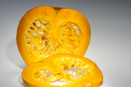 longitudinal: In the foreground on slice of orange pumpkin  We can see also pulp and seeds in the background on the cutting pumpkin with front longitudinal section  Freshly harvest in autumn before shooting on studio  Background in light grey gradation  Stock Photo