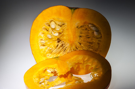 longitudinal: In the foreground on slice of orange pumpkin  We can see also pulp and seeds in the background on the cutting pumpkin with front longitudinal section  Freshly harvest in autumn before shooting on studio  Background in gray gradation