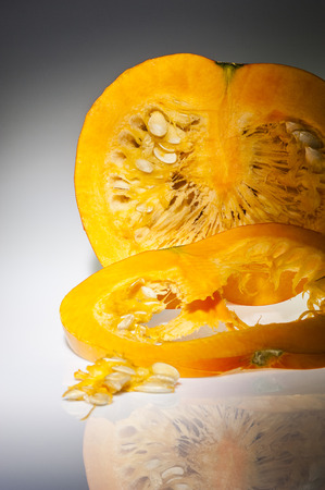 longitudinal: In the foreground on slice of orange pumpkin  We can see also pulp and seeds in the background on the cutting pumpkin with front longitudinal section  Freshly harvest in autumn before shooting on studio  Background with reflections in gray gradation  Stock Photo