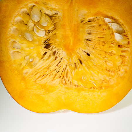 longitudinal: Closeup on longitudinal section of orange pumpkin with pulp and seeds  Shooting studio on white background after freshly harvest in autumn  Square frame