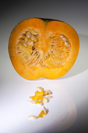 longitudinal: A longitudinal section of orange pumpkin after freshly harvest in autumn   In the foreground some pulp and seeds  Shooting studio on white background with reflections in gray gradation  Stock Photo