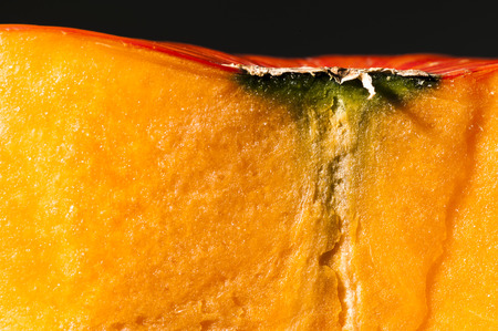 longitudinal: Closeup on a longitudinal section of orange pumpkin after freshly harvest in autumn  We can see with big details pulp and peel  Shooting studio with macro lens on black background