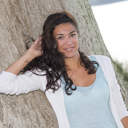 attractive young woman: Portrait of attractive young woman (20s) smiling and looking at camera in nature. Large trunk tree on background. Head and shoulders with one hand behind head. Stock Photo