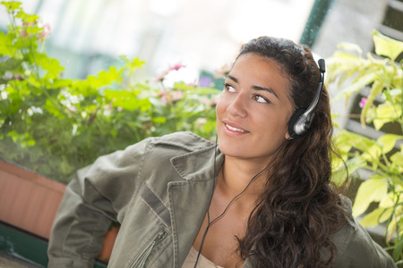 pretty young woman: Brown pretty young woman (20s) listening to music with headphones. She is smiling and looking away. Closeup
