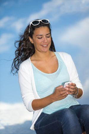 pretty young woman: Pretty young woman (20s) enjoying and looking her smartphone in nature. She seems sitting on clouds with wind into long hairs and blue sky on background.