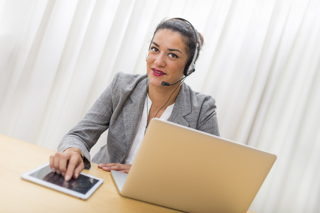 teleoperator: Smiling well-dressed businesswoman with headset on. She is in office behind her laptop computer and using tablet