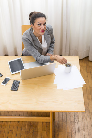 coffeebreak: High angle view on businesswoman looking at camera in office at coffeebreak wood on her desk