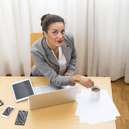 coffeebreak: Portrait with high angle view one businesswoman looking at camera in office at coffeebreak wood on her desk Stock Photo
