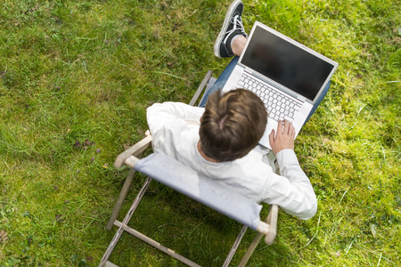 Bird view on smart casual young adult sitting on a chair with laptop computer His wide. He is typing isolated on green grass. Focus on laptop computer. photo