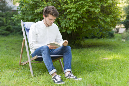 A cute bearded young man with casual clothes reading a book on His knees on a garden chair. He is sitting and studying in a green garden with lush foliage and copy space. photo