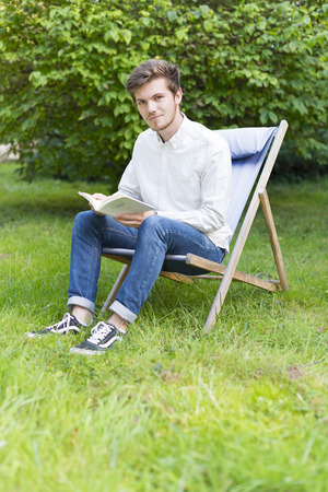 A bearded student sitting (20s) university of reading a book in the garden with lush foliage french. photo