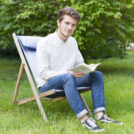 Portrait of sitting bearded young man (20s) reading a book in the garden with lush foliage french. photo