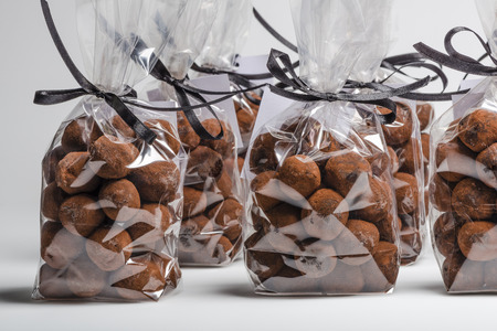 on white chocolate: Group of elegant plastic bags with black ribbon of Christmas chocolate truffles in a row. Shooting on white background in studio.