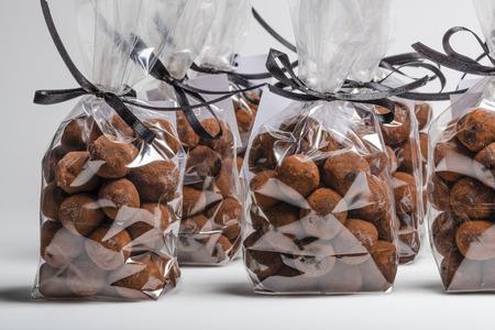 cioccolato natale: Gruppo di eleganti sacchetti di plastica con il nastro nero di tartufi di cioccolato di Natale in una riga. Tiro su sfondo bianco in studio.