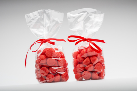 Couple of luxury plastic bags with elegant red ribbons of candies for gift. Shooting on white background in studio.