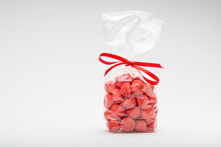 Beautiful candy strawberries bag isolated on white background. Left copy space. Fun composition and lighting. Shooting in studio.