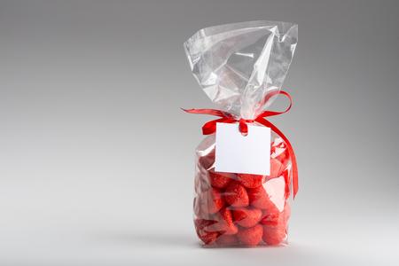 obesidad infantil: las fresas bolsa de pl�stico muy bonito y acidulada aislado sobre fondo gris. Izquierda copia espacio. La etiqueta en blanco. Diversi�n composici�n y la iluminaci�n. Disparos en el estudio.