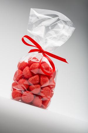 obesidad infantil: El deseo y el deleite de az�car. Bolsa de fresas acidulada con una elegante cinta de color rojo sobre fondo gris. Disparos en el estudio.