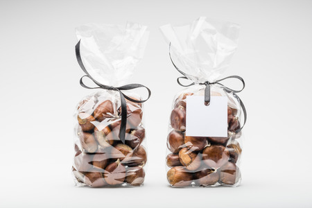 gift bags: Two luxury transparent plastic bags with elegant black ribbons of sweet chestnuts for gift. One blank label. Copy space. Shooting on white background in studio.