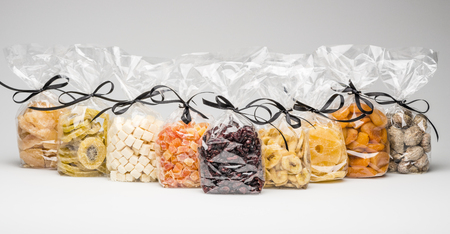 Tasty organic dried fruits collection. Gifts into luxury transparent plastic bags with elegant black ribbons. Shooting in studio on grey background.