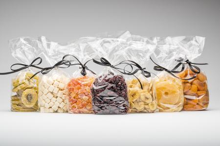 Gemengde verzameling gedroogde vruchten in een elegante plastic zakken met luxe zwarte linten. Giften in een rij. Schieten in de studio met een kopie ruimte op een grijze achtergrond.